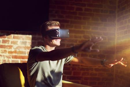 virtual reality simulator: Young man wears grey t-shirt enjoying vr set sitting on sofa, indoor shot