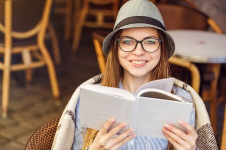 Stylish cheerful girl wears blue shirt, hat and eyeglasses, plaid, reading book in street cafe, outdoors sunny autumn time