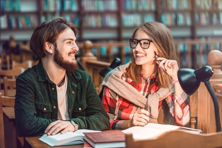 Portrait of two successful students casual stylish, boy and girl in library reading hall, evening time, education concept 版權商用圖片 - 89350445
