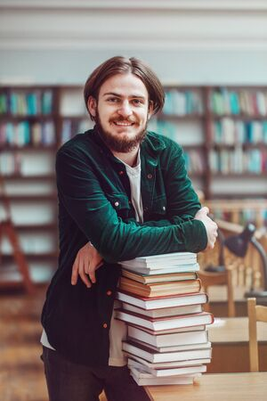 Portrait of young persistent casual student man use a stack of books for studying before bookshelves in library Stock Photo