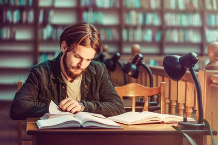 Portrait of young bearded student man reading in a library hall on table with lot of books and lamp, indoor dusk time, education concept