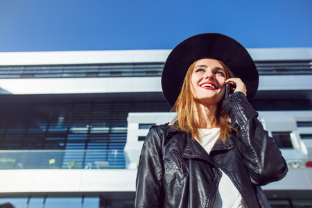 Stylish hipster girl wears black leather jacket and hat talking by phone before modern building