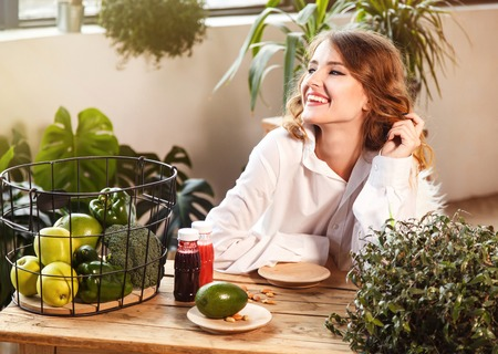 Fair-haired girl sitting down at the table full of healthy food, indoor shot among green plants Banco de Imagens