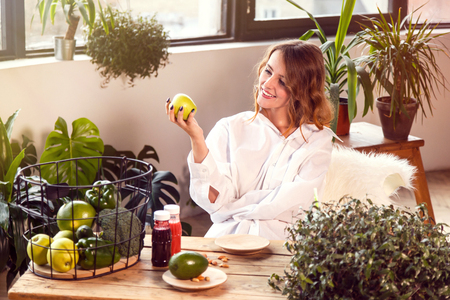 Fair-haired girl smelling a green apple with pleasure at the table full of healthy food, indoor shot among green plants