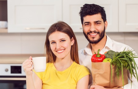 Handsome bearded man holding shopping bag with healthy, nutritious food, in pristine white shirt and slim woman, in yellow t-shirt Stock Photo