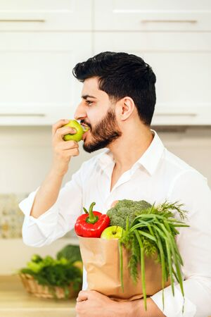 Black-haired bearded man, in smart white shirt, holding shopping pack with fresh, organic food and green apple inthe kitchen