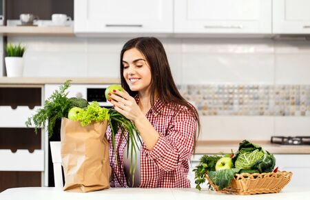 Lovely slim woman, in checked red shirt, unpacking shopping bag with green food near basket with green fruit and vegetables, concept of consuming healthy food