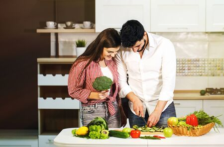 Beautiful couple having fun as cooking, handsome bearded man slicing cucumber, pretty dark-haired woman with broccoli in hand 写真素材