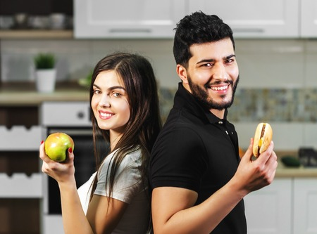 Attractive dark-haired man in black t-shirt and brunette girl hesitating between green apple and tasty hamburger, decides to eat the fresh healthy fruit, concept of choosing Stock Photo