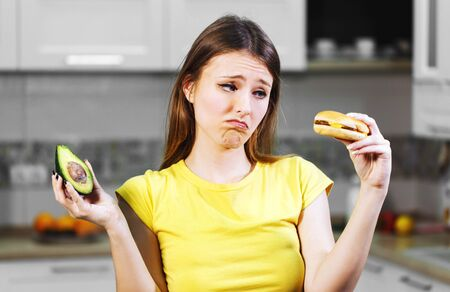 Attractive long-haired woman hesitating between fresh avocado and unhealthy hamburger, decides to have the green nutritious fruit, concept of making choice Stock Photo