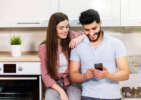 Happy young couple using smartphone, wearing casual clothes, spending time together in light white kitchen Stockfoto