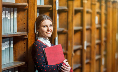 Curious woman standing near library bookshelves with red book