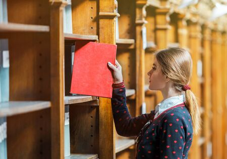 Curious woman pick book near library bookshelves with red book