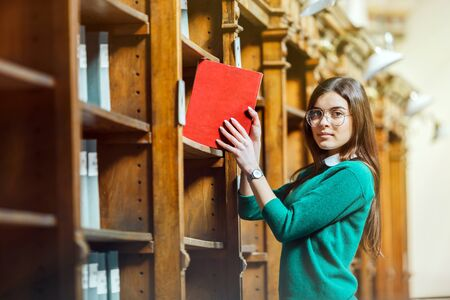 Slender brunette wearing stylish glasses and green sweater holds red book near library bookshelves