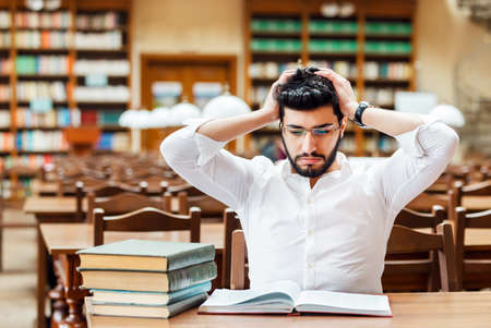 Portrait of young thinking bearded man student with stack of books on the table before bookshelves in the library