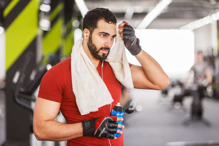Bearded muscular man wears red t-shirt with towel and bottle in the gym, hardworking rest