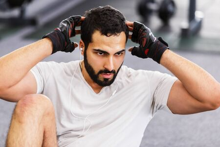 Bearded muscular man wears white t-shirt and black gloves does wring workout in the gym