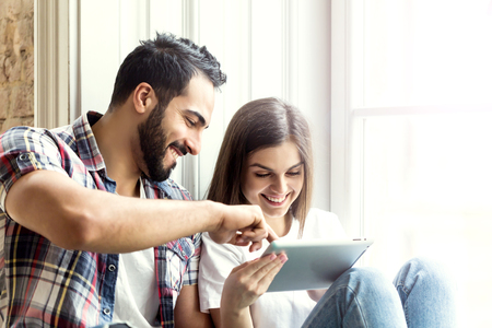 Bearded handsome man and brunette girl sitting on the wide windowsill using tablet computer