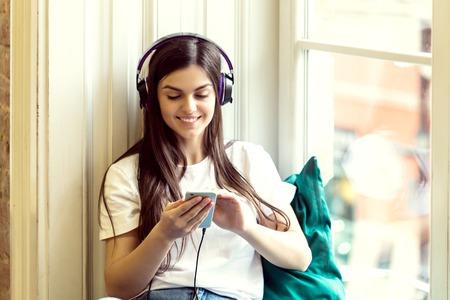 Fille aux cheveux longs porte des écouteurs et un t-shirt blanc écouter de la musique assis sur un large rebord de fenêtre