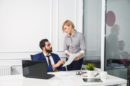 Business workers in white office interior, bearded boss and blonde woman with documents Фото со стока