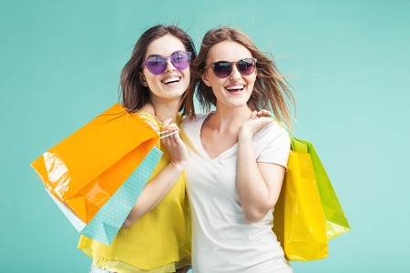 Two beautiful shopaholic smiling girls wears sunglasses holds lot of shopping colorful bags on blue background