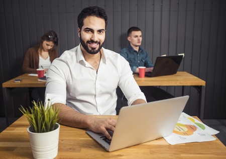 Freelance man with black beard working on laptop before colleagues working on the task, preparing next stage of the project at office desk with graphs