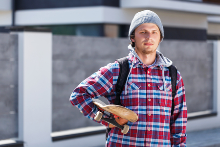 Hipster man dressed in cheked shirt and cap holding skateboard before grey fence, outdoor street portrait Stock Photo