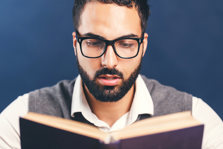 Portrait of eastern arab bearded man reading book before blue background 스톡 콘텐츠