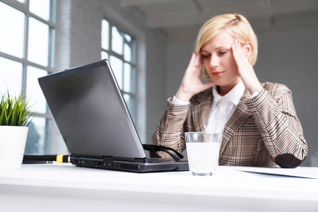 Blonde businesswoman dressed in stylish suit have working headache, using effervescent pill on water in glass, workplace with laptop in white office Stock Photo
