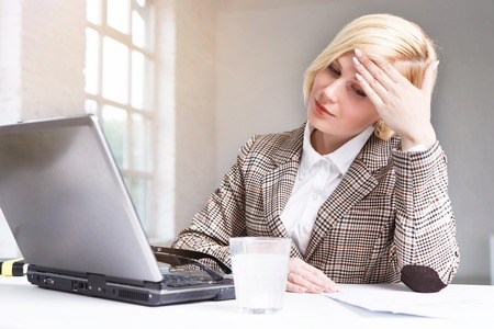Pretty blonde businesswoman stylish suit have working headache, using effervescent pill on water in glass, workplace with laptop in white office