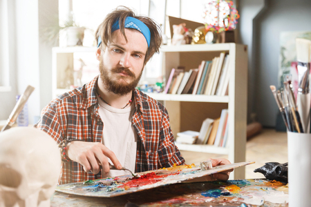 Portrait of a young bearded male artist is holding a brush and mix color oil painting on palette Stockfoto
