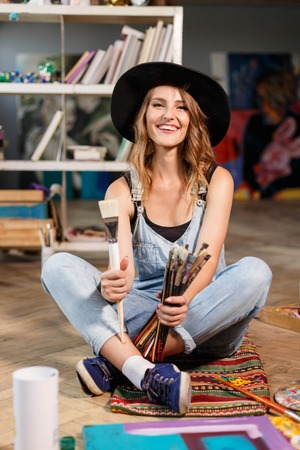 Pretty romantic long-hair female artist in cute black hat holding many brushes and sitting on the floor in contemporary studio with many paintings Stockfoto