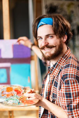 Handsome dark-haired bearded hipster male artist in blue bandana holding palette and staying behind the easel in his contemporary studio with many paintings