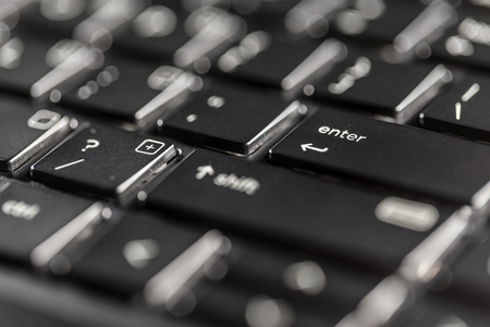 Macro view of black laptop keyboard buttons against back light