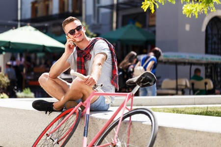 Handsome young hipster man in sunglasses sitting near the bicycle, smiling and speaking on the smartphone in the sunny street Фото со стока