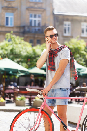 Handsome young hipster man in sunglasses walking with bicycle, smiling and speaking on the smartphone in the sunny street