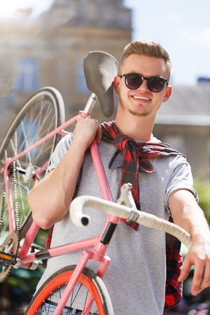 Handsome young hipster man in sunglasses walking with bicycle and smiling in the sunny street Фото со стока