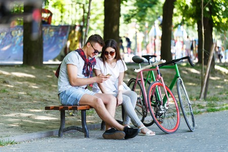 Young couple in love with bicycle sitting on beanch and looking something in the smartphone in the sunny summer park Фото со стока