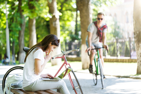 Pretty girl with bicycle sitting on beanch and using laptop in the sunny summer park