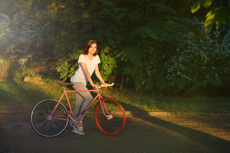 Young pretty romantic girl walking with bicycle on the sunset in green summer park Фото со стока