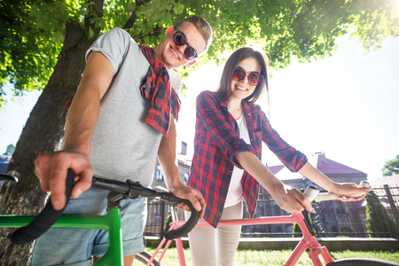 Happy young romantic couple walking with bicycle at green summer park Фото со стока