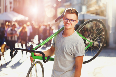 Young hipster light-hair boy in glasses holding green bicycle at sunny summer street