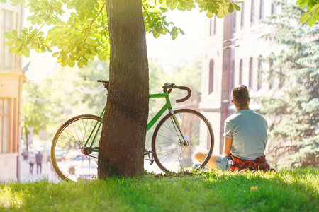 Young stylish hipster boy sitting with bicycle at green sunny summer park