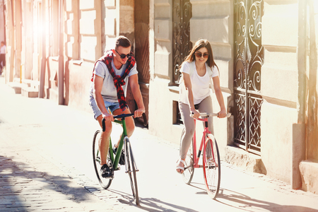 Young stylish hipster boy and romantic long-hair girl in sunglasses ride bicycle and smiling at sunny summer street
