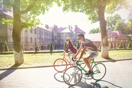 Happy young hipster couple having fun with bicycle at green summer park Фото со стока