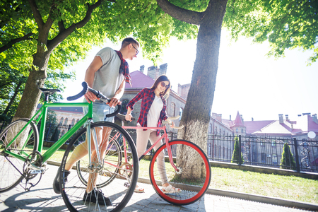 Happy young hipster couple walking with bicycle at green summer park