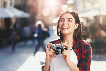 Portrait of young stylish hipster romantic long-hair girl in sunglasses staying with bicycle and holding camera, she admiring of amazing views at sunny summer street