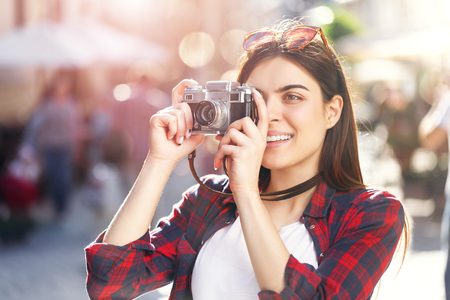 Portrait of young pretty hipster long-hair girl in sunglasses staying with bicycle and making photos of amazing views at sunny summer street Фото со стока