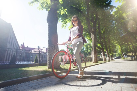 Young beautifull girl walking with pink bicycle in the green summer park Фото со стока