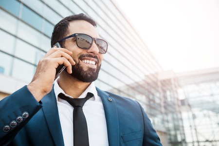 Bearded smiling businessman wears blue suit and sunglasses talking via smartphone before high modern building